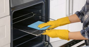 woman-cleaning-oven-in-kitchen-closeup-picture-id942141666